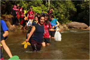 Students crossing a river to reach the waterfall