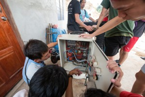 Students checking the electrical connections of the circuit board.